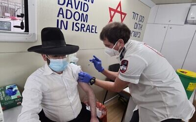 The Magen David Adom mobile vaccination unit inoculates a yeshiva student at an unspecified location, February 16, 2020 (Courtesy)