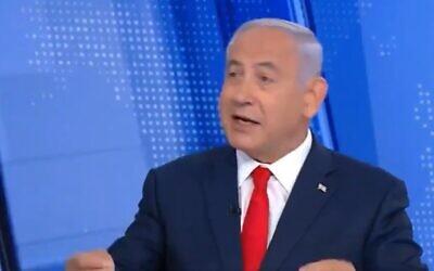 Prime Minister Benjamin Netanyahu waves his arms as he says 'na, na, na, na, na' in interview on February 15, 2020 (Screen grab/Channel 12)