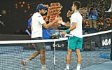 Aslan Karatsev (L) shakes hands with Novak Djokovic (R) at the Australian Open in Melbourne, Australia, Feb. 18, 2021 (Peter Haskin / Australian Jewish News)