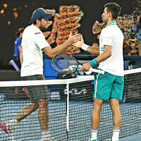 Aslan Karatsev (L) shakes hands with Novak Djokovic (R) at the Australian Open in Melbourne, Australia, Feb. 18, 2021 (Peter Haskin / Australian Jewish News)
