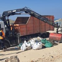 The Environmental Protection Ministry clearing tar from Israel's beaches following a major spill that contaminated the coastline, February 24, 2021. (Environmental Protection Ministry)