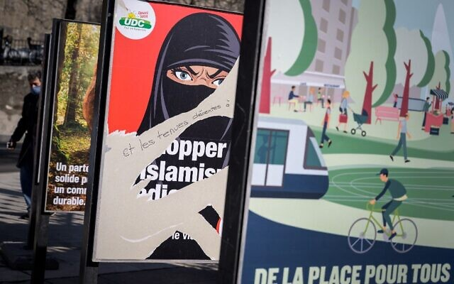 """A picture taken on March 1, 2021 in Geneva shows a torn electoral poster in favor of a """"burqa ban"""" initiative reading in French: """"Stop extremism!"""" ahead of a nationwide vote by Swiss citizen on whether they want to ban face coverings in public on March 7, 2021, as part of the country's famous direct democratic system. (Fabrice COFFRINI / AFP)"""