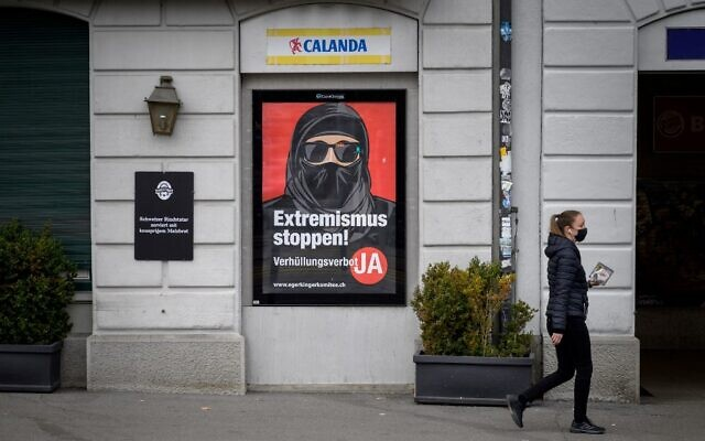 A woman wearing a protective facemask, as a preventive measure against the Covid-19 (the novel coronavirus), walks past a campaign poster, in favour of the 'burqa ban' initiative reading in German: 'Stop extremism!' on March 3, 2021 in the streets of Zurich, ahead of a nationwide vote on March 7, 2021 by Swiss citizen on whether to ban full facial coverings in public places. (Fabrice COFFRINI / AFP)