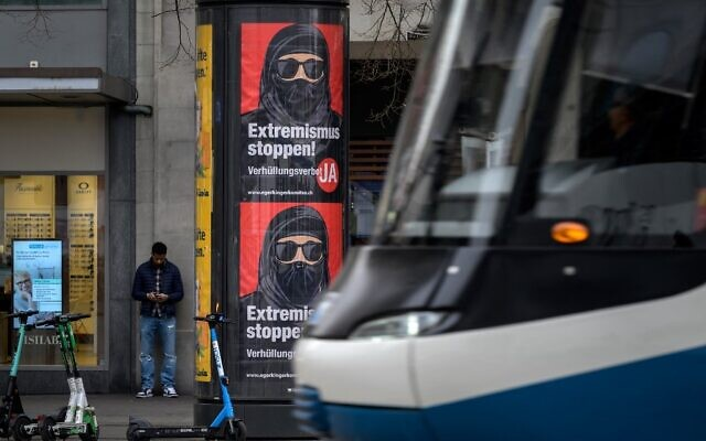 A tram passes by campaign posters in favor of the 'burqa ban' initiative reading in German: 'Stop extremism!' on March 3, 2021 in the streets of Zurich, ahead of a nationwide vote on March 7, 2021, by Swiss citizen on whether to ban full facial coverings in public places. (Fabrice COFFRINI / AFP)