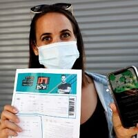 """An attendee shows off a """"green pass"""" (proof of being fully vaccinated against COVID-19 coronavirus disease) upon arrival at Bloomfield Stadium in Tel Aviv, on March 5, 2021, before attending a """"green pass concert"""" for the vaccinated, organized by the Tel Aviv municipality. (Jack Guez/AFP)"""