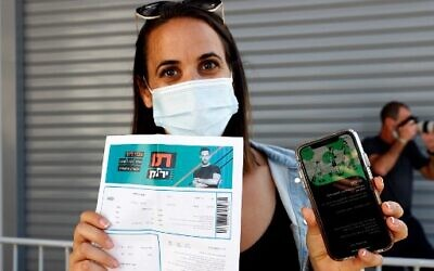 "An attendee shows off a ""green pass"" (proof of being fully vaccinated against COVID-19 coronavirus disease) upon arrival at Bloomfield Stadium in Tel Aviv on March 5, 2021, before attending a ""green pass concert"" for the vaccinated, organized by the Tel Aviv municipality. (Photo by JACK GUEZ / AFP)"