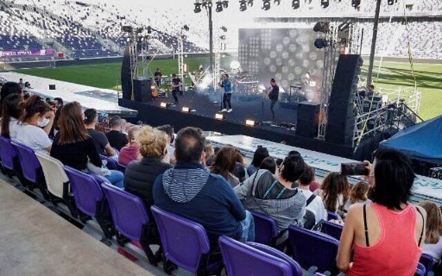 "People vaccinated against COVID-19 coronavirus disease and holding a ""green pass"" (proof of being fully vaccinated) attend a ""green pass concert"" organised by the Tel Aviv municipality at Bloomfield Stadium in the Israeli Mediterranean coastal city on March 5, 2021. (Photo by JACK GUEZ / AFP)"