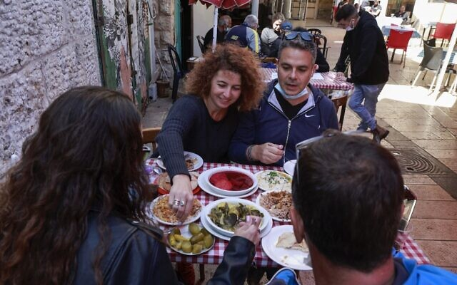 """People eat at the Azura restaurant in Jerusalem, on March 7, 2021, after Israel reopened restaurants, bars and cafes to vaccinated """"green pass"""" holders (Menaham Kahana / AFP)"""