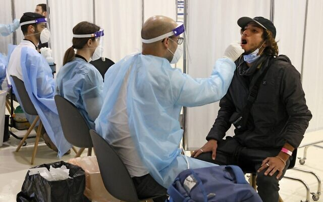 Travelers sit for the COVID test at Ben Gurion Airport on March 8, 2021, upon their arrival from New York. (JACK GUEZ / AFP)