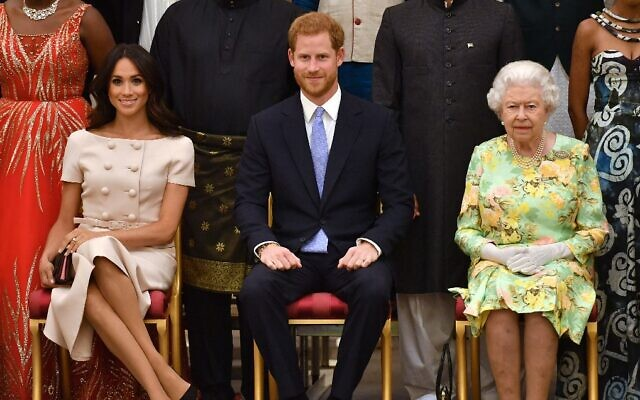 Left to right: Meghan Markle, Prince Harry, and Britain's Queen Elizabeth II pose for a picture during the Queen's Young Leaders Awards Ceremony, at Buckingham Palace in London, June 26, 2018. (John Stillwell/Pool/AFP/File)