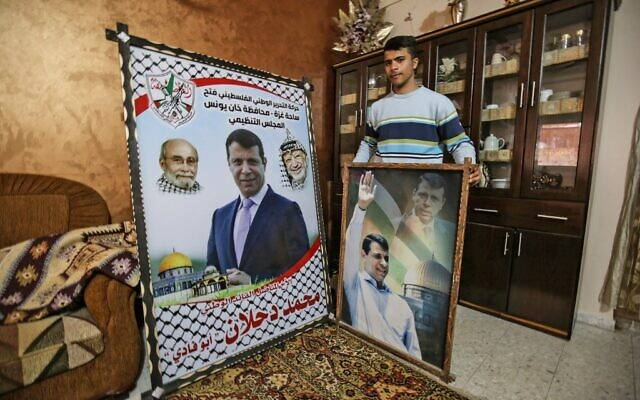 A member of the Dahlan family, displays pictures of exiled Palestinian politician Mohammed Dahlan, at their family home in Khan Yunis, in the southern Gaza Strip on February 24, 2021. (SAID KHATIB / AFP)