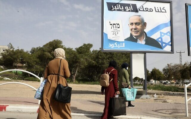 Bedouin women walk past campaign billboards for Israel's right-wing Likud party bearing a picture of its leader Prime Minister Benjamin Netanyahu in the Bedouin town of Rahat near the southern Israeli city of Beersheba on March 10, 2021. (HAZEM BADER/AFP)