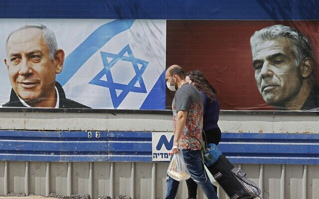 People walk past an electoral billboard for the Likud party bearing a portrait of its leader Prime Minister Benjamin Netanyahu (L), and opposition Yesh Atid party leader Yair Lapid, in Tel Aviv, on March 12, 2021, ahead of the March 23 general election. (JACK GUEZ / AFP)