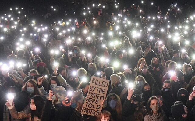 Well-wishers turn on their phone torches as they gather at a band-stand where a planned vigil in honor of murder victim Sarah Everard was cancelled after police outlawed it due to Covid-19 restrictions, on Clapham Common, south London on March 13, 2021  (JUSTIN TALLIS / AFP)