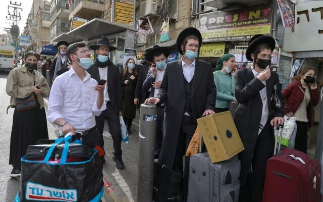 People wait at a bus stop in an ultra-Orthodox Jewish neighborhood in Jerusalem, on March 11, 2021 (MENAHEM KAHANA / AFP)