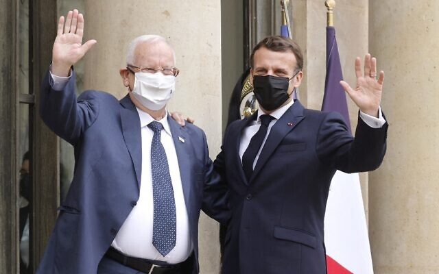 French President Emmanuel Macron (R) and President Reuven Rivlin wave at the Elysee Palace in Paris on March 18, 2021. (Ludovic Marin/AFP)