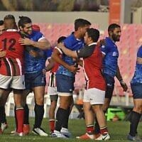 Israeli (blue) and Emirati rugby players greet each other after their first friendly match in Dubai on March 19, 2021. (Karim SAHIB/AFP)