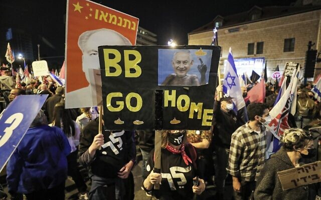"A protester holds a sign reading 'BB GO HOME' depicting Israeli PM Benjamin Netanyahu as the character 'ET' from the 1980s film. The poster behind that depicts Netanyahu as China's late leader Mao Zedong (""Netanmao""). Saturday's demonstration near the Israeli prime minister's residence in Jerusalem on March 20, 2021 was the final protest ahead of national elections on March 23. (EMMANUEL DUNAND / AFP)"