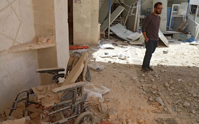 A man stands amid the debris at the entrance of a field hospital in the the village of Atareb in the northern Syrian province of Aleppo on March 21, 2021, after it was reportedly targeted by regime shelling. (AAREF WATAD / AFP)