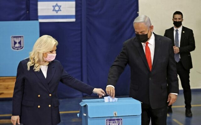 Prime Minister Benjamin Netanyahu and his wife Sara cast their ballots at a polling station in Jerusalem on March 23, 2021 in the fourth national election in two years. (RONEN ZVULUN / POOL / AFP)