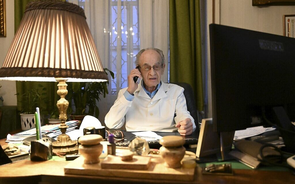 97-year-old Hungarian doctor Istvan Kormendi speaks on phone in his doctor's office at his home in Budapest on March 22, 2021. (ATTILA KISBENEDEK / AFP)