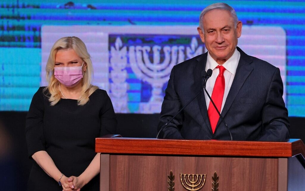 Prime Minister Benjamin Netanyahu and his wife Sara address supporters at  the Likud election party in Jerusalem, early on March 24, 2021, after the end of voting in the fourth national election in two years. (Emmanuel Dunand/AFP)