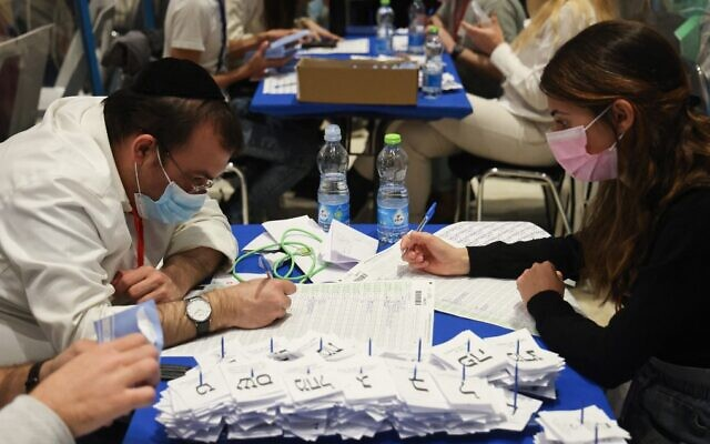 Election workers count ballots in Jerusalem on March 25, 2021. (Emmanuel Dunand/AFP)