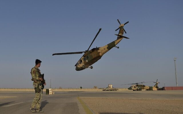 In this photograph taken on March 25, 2021 an Afghan Commandos (ANA) soldier stands guard as an Afghan Air Force Black Hawk helicopter takes off at the Shorab Military Camp in Lashkar Gah, in the Afghan province of Helmand. (WAKIL KOHSAR / AFP)