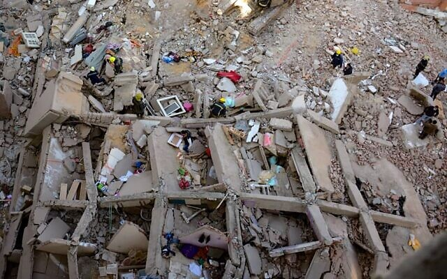People and rescuers gather around the rubble of a building that collapsed in the popular area of Gesr Giza, east of the Egyptian capital Cairo, on March 27, 2021 (AFP)