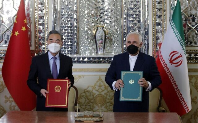"Iranian Foreign Minister Mohammad Javad Zarif (R) and his Chinese counterpart Wang Yi, pose for a picture after signing an agreement in the capital Tehran, on March 27, 2021. Iran and China signed what state television called a ""25-year strategic cooperation pact"" on today as the US rivals move closer together. (AFP)"