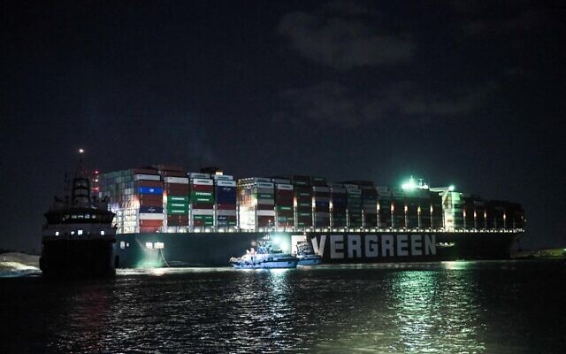 This picture taken late on March 27, 2021 shows a view of tugboats by the Panama-flagged MV 'Ever Given' container ship, which has been wedged diagonally across the span of the canal about six kilometers north of the Suez Canal's entrance by the Red Sea port city of Suez since March 23, blocking the waterway in both directions. (Ahmed HASAN / AFP)