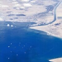 """An aerial view taken on March 27, 2021 from the porthole of a commercial plane shows stranded ships waiting in queue in the Gulf of Suez to cross the Suez Canal at its southern entrance near the Red Sea port city of Suez, as the waterway remains blocked by the Panama-flagged container ship """"MV Ever Given"""", which has remained wedged sideways about six kilometres north of the canal's entrance impeding all flowing traffic since March 23 (Mahmoud KHALED / AFP)"""