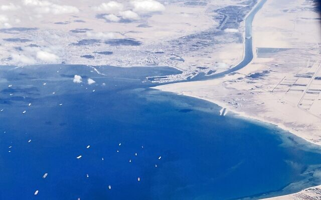 "An aerial view taken on March 27, 2021 from the porthole of a commercial plane shows stranded ships waiting in queue in the Gulf of Suez to cross the Suez Canal at its southern entrance near the Red Sea port city of Suez, as the waterway remains blocked by the Panama-flagged container ship ""MV Ever Given"", which has remained wedged sideways about six kilometres north of the canal's entrance impeding all flowing traffic since March 23 (Mahmoud KHALED / AFP)"