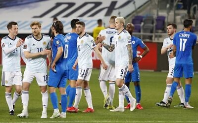 Players greet each other at the end of the 2022 FIFA World Cup qualifier group F football match between Israel and Scotland at Bloomfield stadium in the Israeli Mediterranean coastal city of Tel Aviv on March 28, 2021. (JACK GUEZ / AFP)