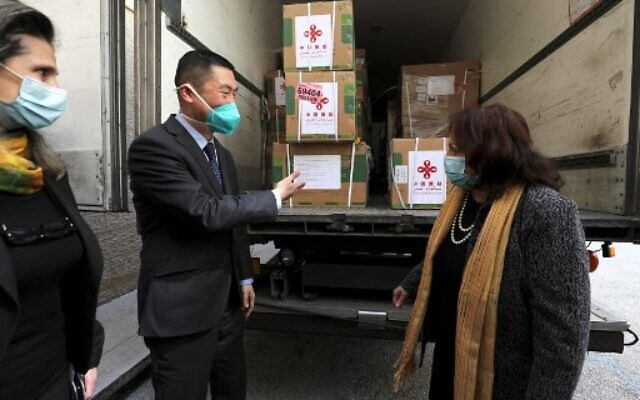 Chinese Ambassador Guo Wei (L) speaks with Palestinian Health Minister Mai al-Kaila during the unloading of a shipment of the Sinopharm COVID-19 vaccines donated by the Chinese government in the city of Ramallah in the West Bank, on March 29, 2021. (ABBAS MOMANI/AFP)