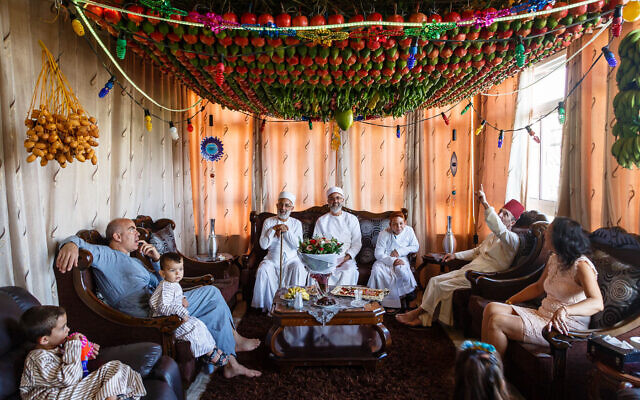 Samaritans sitting under their Sukkah decorated with fruits and vegetables during Sukkot holiday. Nablus, Palestinian territories, October 2017. (Yadid Levy)