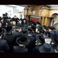 Hundreds of men crowded into a study hall for the funeral of Rabbi Yechezkel Roth on March 7, 2021. (Screenshot from BoroPark24 via JTA)
