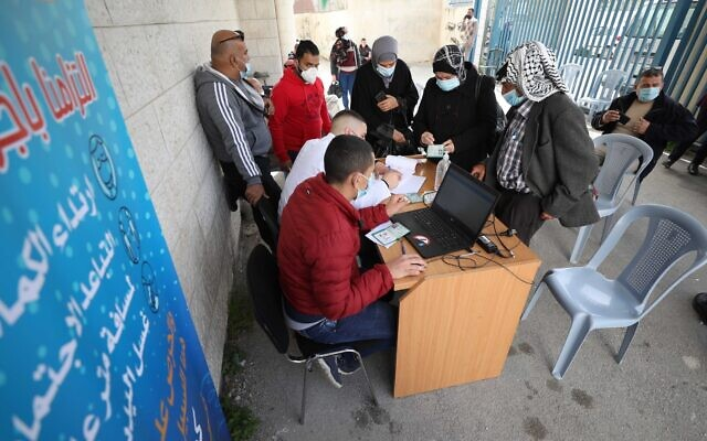 Palestinian Authority employees sign in West Bank Palestinians to be vaccinated against the coronavirus on March 21, 2021 (WAFA)