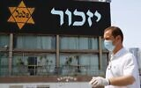 Illustrative: A man in a mask and protective gear stands near a banner depicting a Holocaust-era yellow Star of David, in Tel Aviv on April 21, 2020. (Jack Guez/AFP via Getty Images)