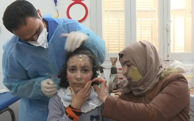 Eight-year-old Maram slips on a 3D-printed mask developed by medical charity Doctors Without Bordersthat covers her face and treats her severe burns from a blaze at a Gaza bakery. (Screen capture/AFP)