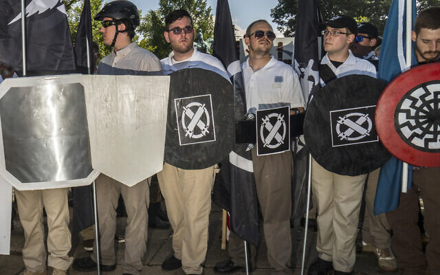 In this August 12, 2017 photo, James Alex Fields Jr., center left, holds a black shield in Charlottesville, Virginia, where a white supremacist rally took place. Fields was later charged with second-degree murder and other counts after authorities say he plowed a car into a crowd of people protesting the white nationalist rally earlier in the day. (Go Nakamura via AP)
