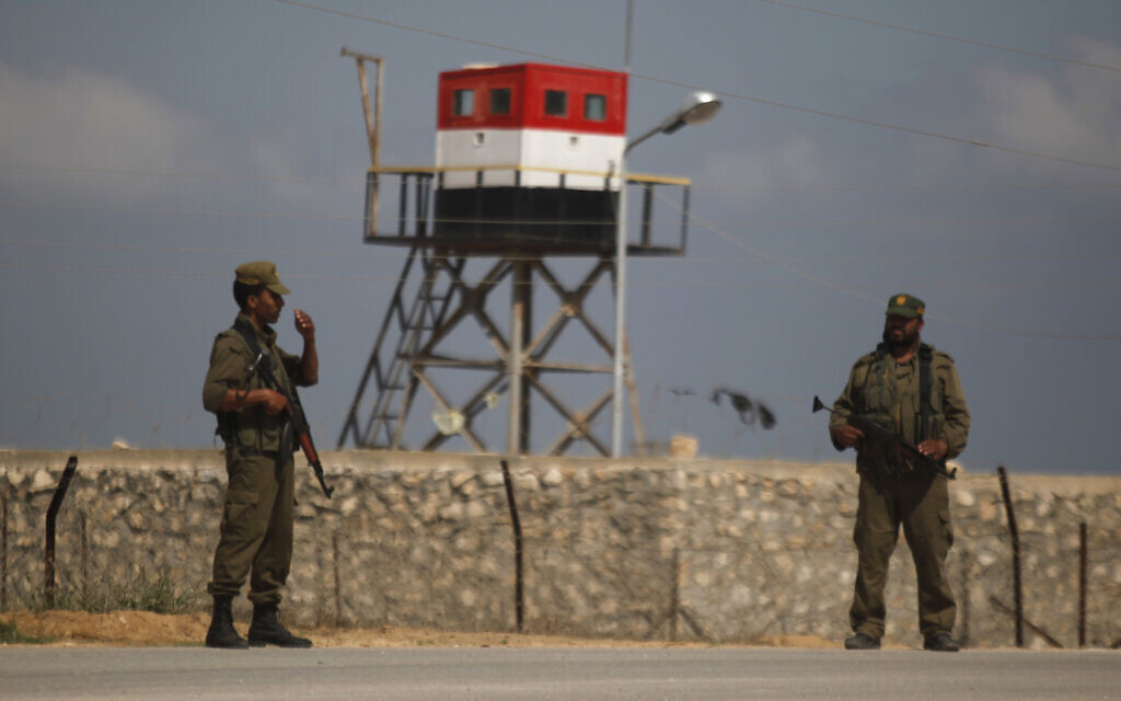 Palestinian Hamas guards stand near an Egyptian watchtower on the border with Egypt in Rafah, southern Gaza Strip. (AP/Hatem Moussa)