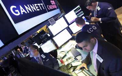 In this Aug. 5, 2014, file photo, specialist Michael Cacace, foreground right, works at the post that handles Gannett on the floor of the New York Stock Exchange. J(AP Photo/Richard Drew)