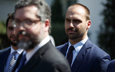 Eduardo Bolsonaro, son of Brazilian President Jair Bolsonaro, right, listens as Brazilian Foreign Minister Ernesto Araujo speaks with reporters after meeting with President Donald Trump at the White House, August 30, 2019, in Washington. (AP Photo/Evan Vucci)
