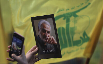 Illustrative: A supporter of the Hezbollah terror group uses her mobile phone to takes a picture of photo of slain Iranian Revolutionary Guard Gen. Qassem Soleimani during a ceremony marking the anniversary of the assassination of Hezbollah leaders, Abbas al-Moussawi, Ragheb Harb and Imad Mughniyeh and the end of a 40-day Muslim mourning period for Soleimani, in the southern suburb of Beirut, Lebanon, February 16, 2020. (AP Photo/Hassan Ammar)