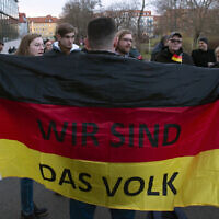 People attend a so called 'A light for democracy' silent demonstration, initiated by the far-right Alternative for Germany (AfD) party in Erfurt, central Germany, Tuesday, March 3, 2020. The words at the German flag read 'We are the people'. (AP Photo/Jens Meyer)