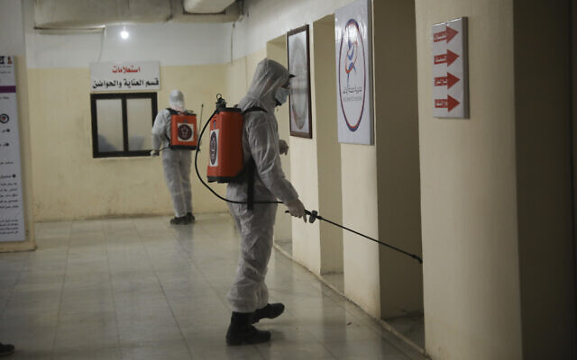 Illustrative: Members of a humanitarian aid agency disinfect Ibn Sina hospital as prevention against coronavirus in the city of Idlib, Syria, March 19, 2020. (AP Photo/Ghaith Alsayed)