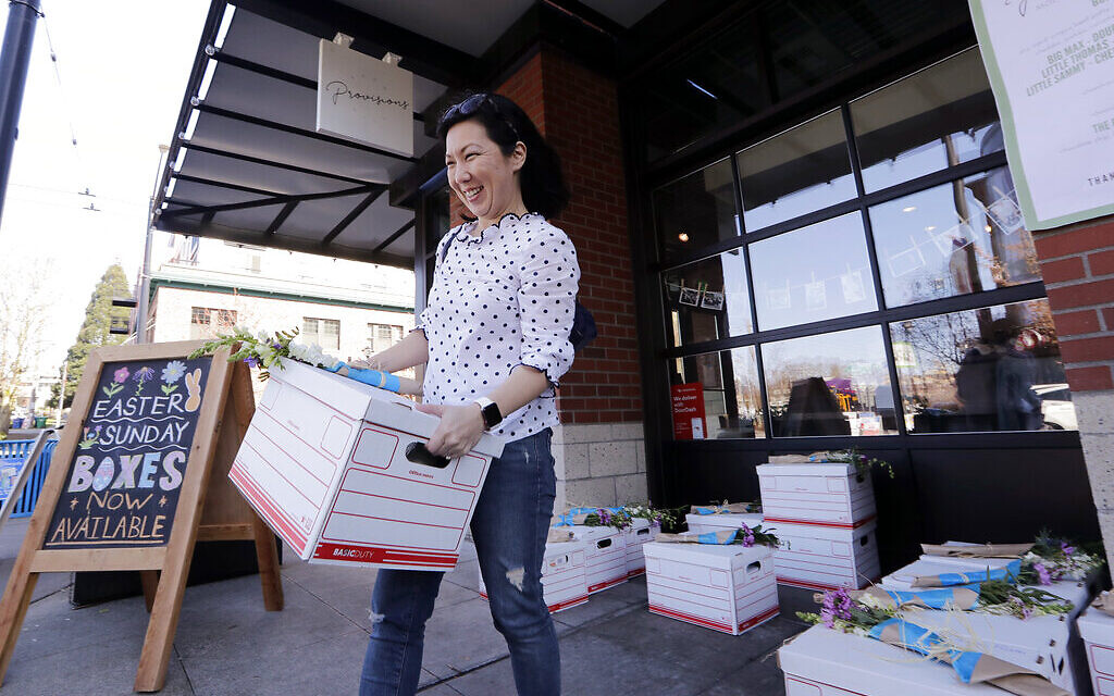 Jessica Choe picks up a 'seder to go' kit packed and left with dozens of others outside a local cafe ahead of her family's Passover meal April 8, 2020, in Seattle. (AP Photo/Elaine Thompson)
