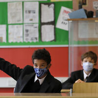 Year seven pupils Henry Holness, left, and Eddie Favell in class during their first day at Kingsdale Foundation School in London, September 3, 2020. (AP Photo/Kirsty Wigglesworth)