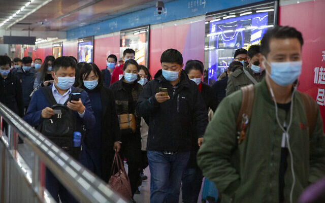 Commuters look at their smartphones as they walk through a subway station in Beijing, Thursday, Oct. 29, 2020. (AP Photo/Mark Schiefelbein)